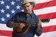 Man playing his mandolin in front of American flag, horizontal