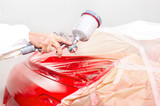 auto engineer paiting a red paint on  car in special booth