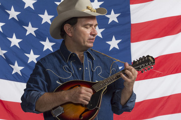 Man playing mandolin in front of American flag, horizontal