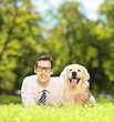 Guy lying on a green grass and hugging his dog in a park