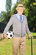 Senior man with hat holding a soccer ball in a park