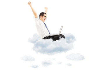 Happy young businessman flying on clouds with laptop