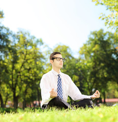 Young businessperson meditating seated on a grass in a park