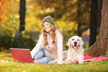 Young female in a park with her dog working on a laptop