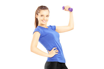 Young woman in sports outfit lifting a dumbbell