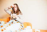 Sick young woman drinking tea on sofa