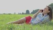 Young woman lying on the grass and talking on mobile phone