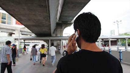 Asian male using smart in urban scene time lapse