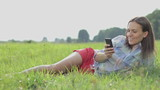 Young woman lying on the grass and sending sms