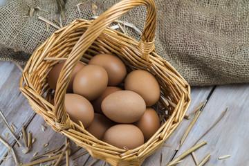 Recolectando huevos frescos en una cesta de mimbre