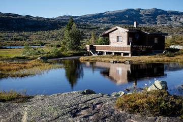 small hut at norwegian lake in hardanger vidda