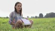 Young smiling woman with laptop computer sitting on the grass