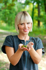 attractive woman holding acorns outside