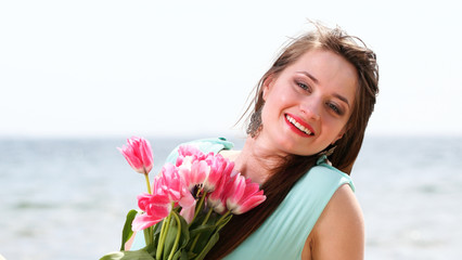 young beautiful woman portrait on the beach bunch flower