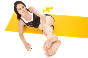 Woman fitness yellow mat lay legs side