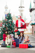 Santa Claus And Children With Gifts By Christmas Tree