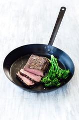 Juicy steak on black pan with fresh green vegetables