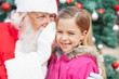 Santa Claus Whispering In Happy Girl's Ear