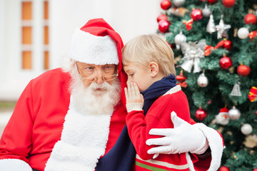 Boy Whispering In Santa Claus's Ear