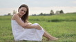 Woman sitting on the meadow and gently touching her skin