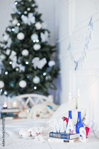 Decorated Christmas tree and gift, candles, pillows in room