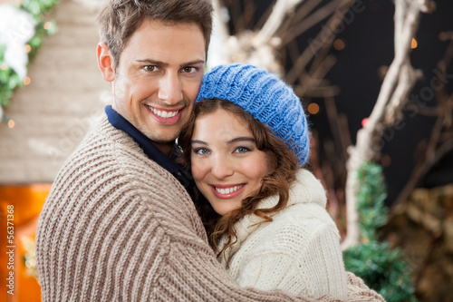Happy Couple Embracing In Christmas Store