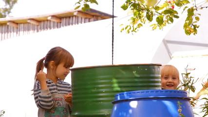 две девочки играют в саду у больших бочек с водой