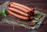 Smoked sausages with basil leaves on a rustic wooden background