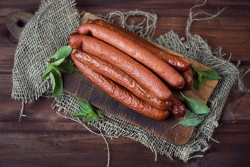 Smoked sausages, rustic wooden background, view from above