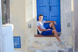 Young man sitting near old blue door of Emporio village on the