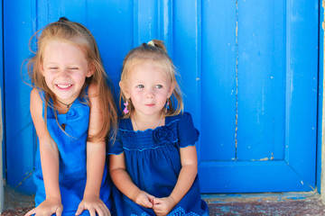 Closeup of Little adorable girls sitting near old blue door in