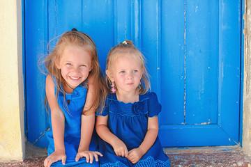 Portrait of Little adorable girls sitting near old blue door in