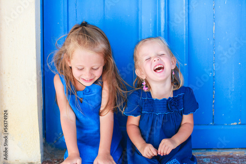 Portrait of Little smiling girls sitting near old blue door in