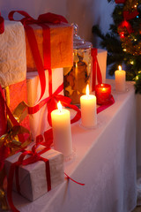 Many gifts near a Christmas tree in the candlelight