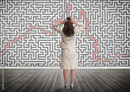 Puzzled businesswoman looking at a maze