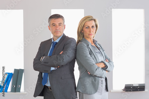 Two unsmiling businesspeople looking at camera standing back to