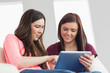 Two happy girls sitting on a sofa using a tablet pc