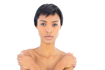 Unsmiling black haired woman covering her shoulders