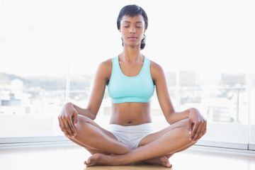 Meditative black haired woman doing yoga
