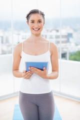 Smiling sporty model holding tablet pc
