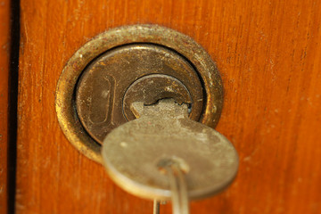 Old antique key in lock of wooden cabinet