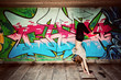 Stylish girl in a dance pose against graffiti wall