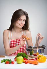 Smiling woman in an apron seasoning soup with paprika