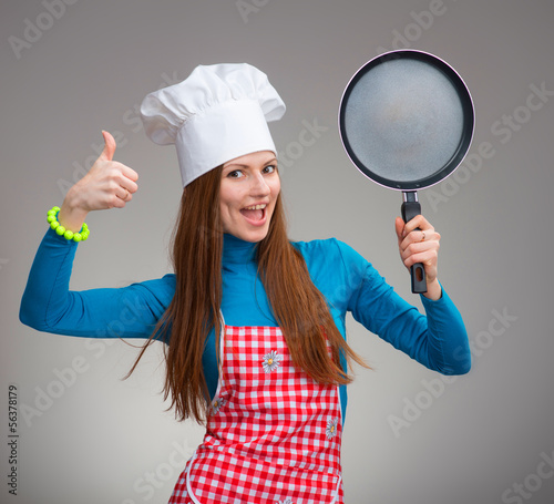 Portrait of a happy woman in chef's hat with the pan