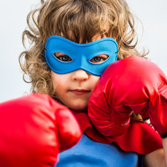Superhero kid wearing boxing gloves. Girl power and feminism
