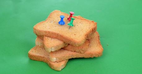 Pushpins Toast bread on green background