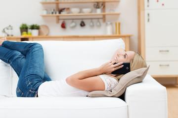 frau liegt auf dem sofa und telefoniert mit ihrem handy