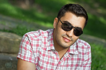 Young cute turkish man in a park, portrait