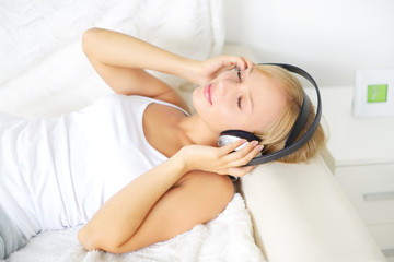 Young attractive girl listening to music in headphones
