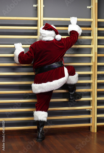 santa claus exercising wh wall bars,Christmas Time preparation